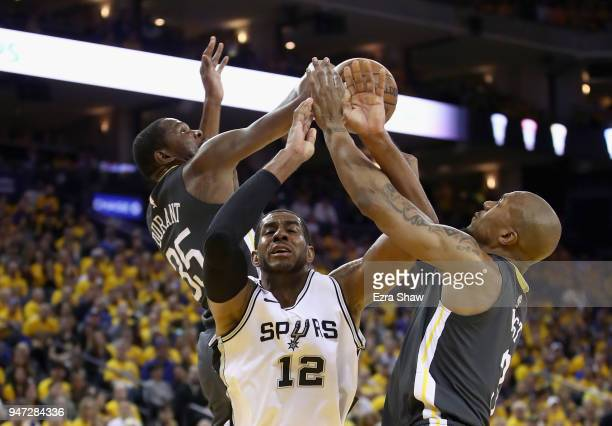 Kevin Durant and David West of the Golden State Warriors strip the ball from LaMarcus Aldridge of the San Antonio Spurs during Game 2 of Round 1 of...