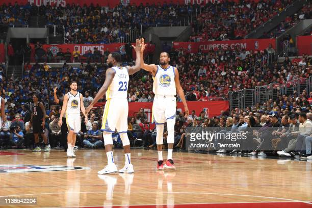 Kevin Durant and Draymond Green of the Golden State Warriors exchange hifives during Game Four of Round One of the 2019 NBA Playoffs against the LA...