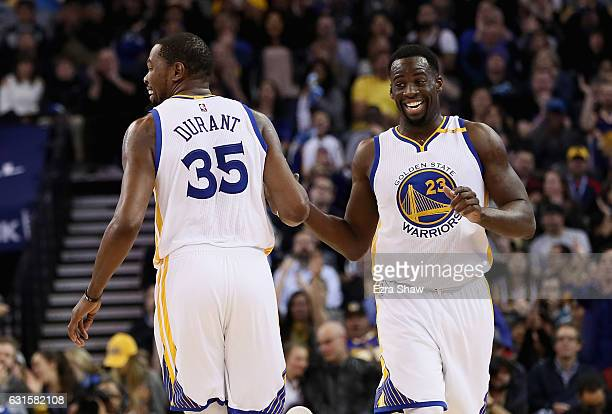 Kevin Durant and Draymond Green of the Golden State Warriors smile as the run back down court during their game against the Detroit Pistons at ORACLE...