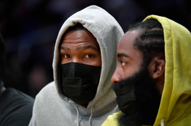 Kevin Durant and James Harden of the Brooklyn Nets follow the action from the bench during a preseason game against the Los Angeles Lakers at Staples...