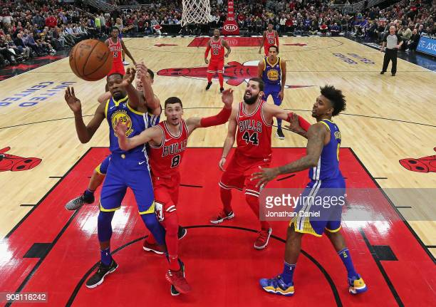 Kevin Durant and Klay Thompson of the Golden State Warriors battle for a rebound with Zach LaVine of the Chicago Bulls at the United Center on...