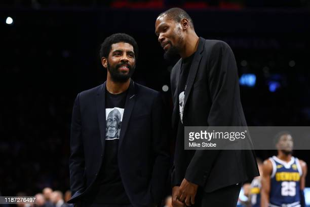 Kevin Durant and Kyrie Irving of the Brooklyn Nets share a laugh during the game against the Denver Nuggets at Barclays Center on December 08 2019 in...