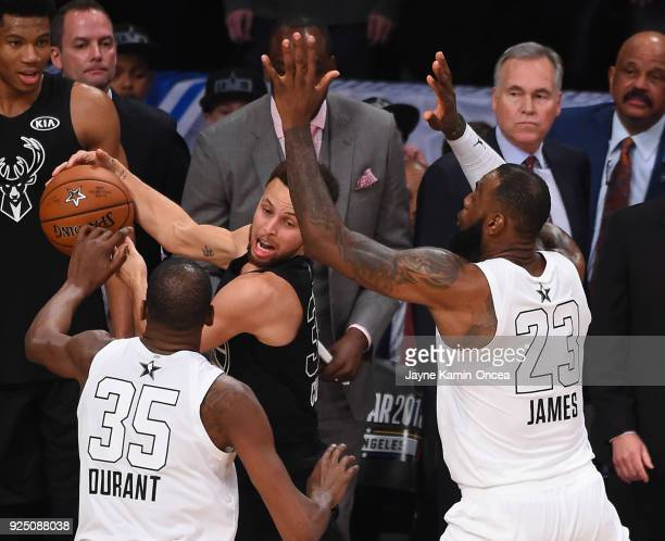 Kevin Durant and LeBron James of Team Lebron defend Stephen Curry during the final seconds of the fourth quarter preventing him from making a shot to...