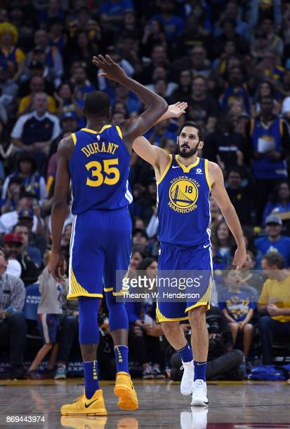 Kevin Durant and Omri Casspi of the Golden State Warriors after a score against the Detroit Pistons during an NBA basketball game at ORACLE Arena on...