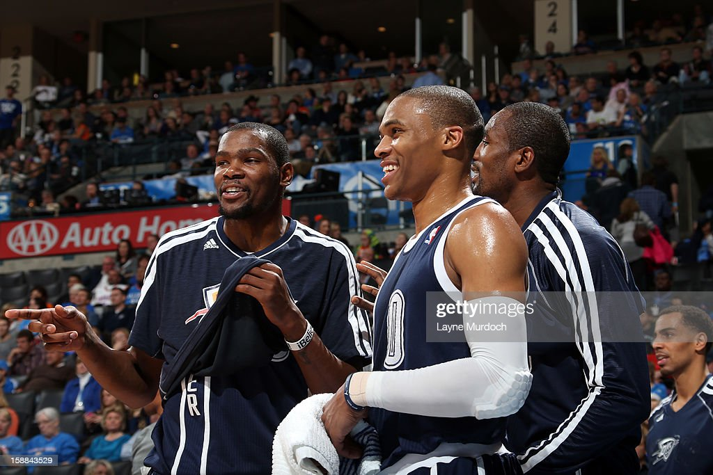 Kevin Durant #35 and Russell Westbrook #0 of the Oklahoma City Thunder both smile while looking at a play against the Phoenix Suns during an NBA game on December 31, 2012 at the Chesapeake Energy Arena in Oklahoma City, Oklahoma.