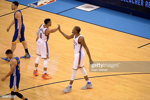 Kevin Durant and Russell Westbrook of the Oklahoma City Thunder high five each other during the game against the Golden State Warriors in Game Three...