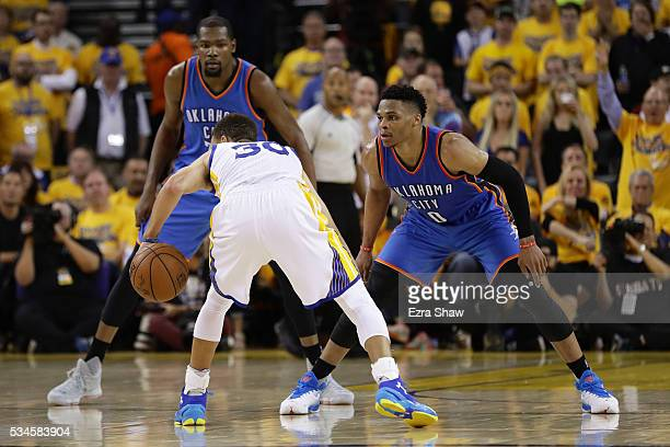 Kevin Durant and Russell Westbrook of the Oklahoma City Thunder defend against Stephen Curry of the Golden State Warriors during Game Five of the...