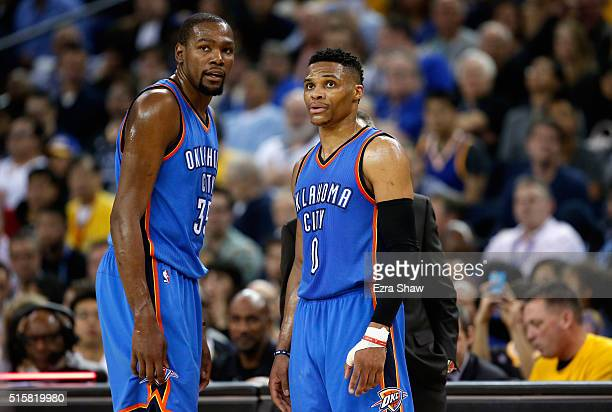Kevin Durant and Russell Westbrook of the Oklahoma City Thunder talk to head coach Billy Donovan during their game against the Golden State Warriors...
