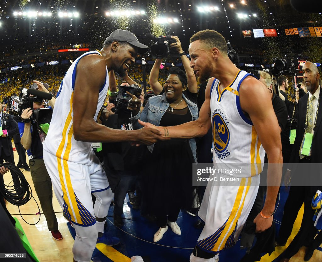 Kevin Durant #35 and Stephen Curry #30 of the Golden State Warriors celebrate after winning the 2017 NBA Finals on June 12, 2017 at ORACLE Arena in Oakland, California.