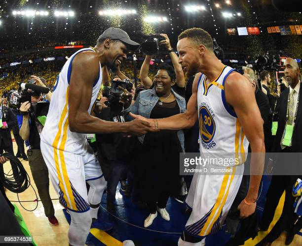 Kevin Durant and Stephen Curry of the Golden State Warriors celebrate after winning the 2017 NBA Finals on June 12 2017 at ORACLE Arena in Oakland...