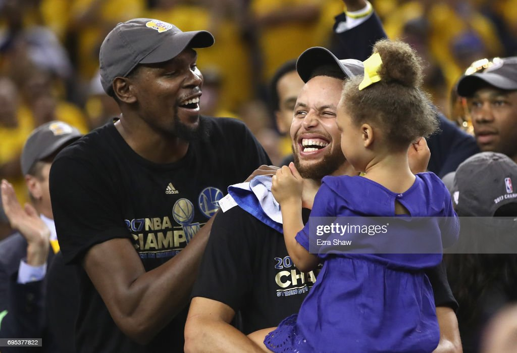 Kevin Durant #35 and Stephen Curry #30 of the Golden State Warriors celebrate after defeating the Cleveland Cavaliers 129-120 in Game 5 to win the 2017 NBA Finals at ORACLE Arena on June 12, 2017 in Oakland, California.