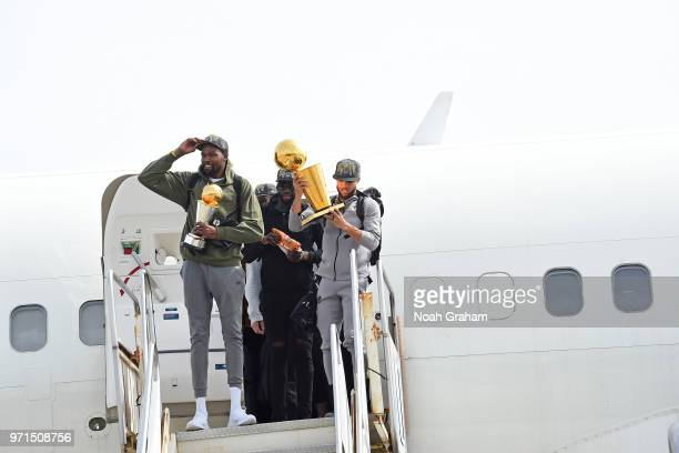 Kevin Durant and Stephen Curry of the Golden State Warriors exit the plane with the Larry O'Brien Championship Trophy and the Bill Russell Finals MVP...