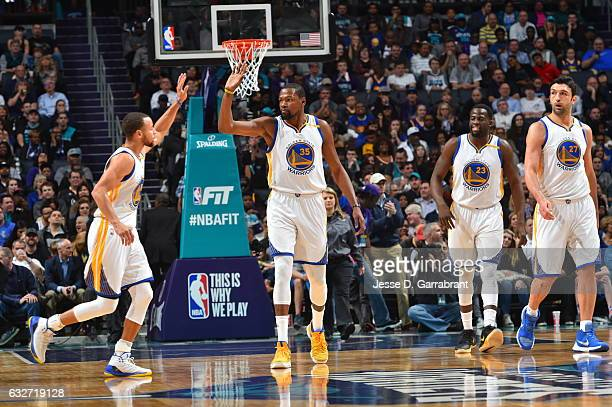 Kevin Durant and Stephen Curry of the Golden State Warriors give each other high fives after a play against the Charlotte Hornets at Spectrum Center...