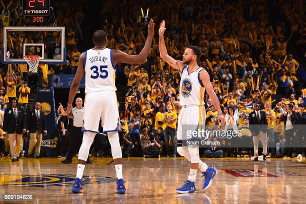 Kevin Durant and Stephen Curry of the Golden State Warriors high five during the game against the Portland Trail Blazers during the Western...