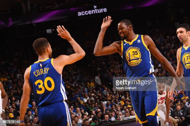 Kevin Durant and Stephen Curry of the Golden State Warriors high five during the game against the Detroit Pistons on October 29 2017 at ORACLE Arena...