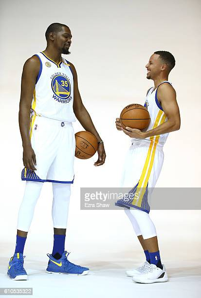 Kevin Durant and Stephen Curry of the Golden State Warriors joke around while they pose for NBA team photographer Noah Graham during the Golden State...