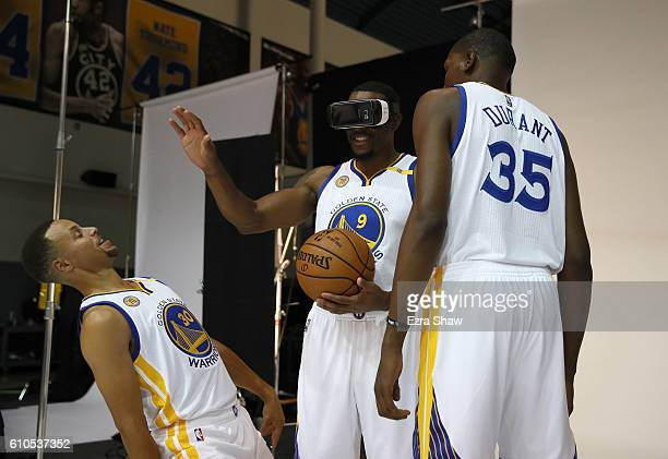 Kevin Durant and Stephen Curry of the Golden State Warriors joke with Andre Iguodala while he wears a virtual reality viewer during the Golden State...