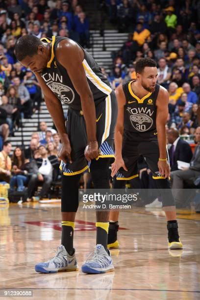 Kevin Durant and Stephen Curry of the Golden State Warriors look on during the game against the Boston Celtics on January 27 2018 at ORACLE Arena in...