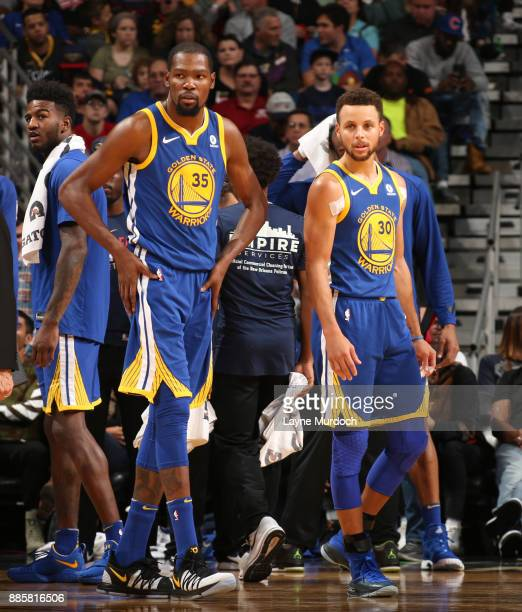 Kevin Durant and Stephen Curry of the Golden State Warriors looks on during the game against the New Orleans Pelicans on December 4 2017 at Smoothie...