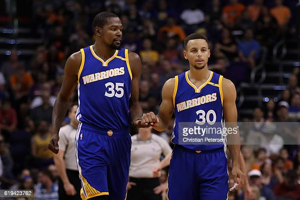 Kevin Durant and Stephen Curry of the Golden State Warriors talk as they walk down court during the first half of the NBA game against the Phoenix...
