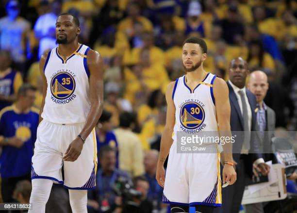 Kevin Durant and Stephen Curry of the Golden State Warriors walk back on to the court after a time out during their game against the San Antonio...
