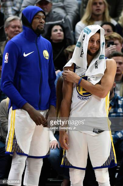 Kevin Durant and teammate Stephen Curry of the Golden State Warriors look on from the bench near the end of a game won by the Utah Jazz 12999 at...