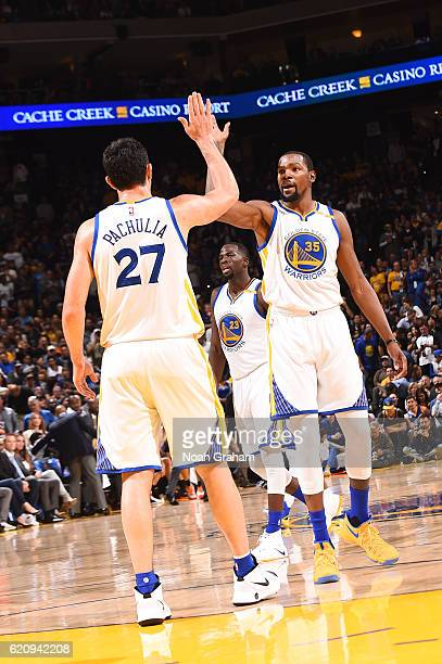 Kevin Durant and Zaza Pachulia of the Golden State Warriors highfive during a game against the Oklahoma City Thunder on November 3 2016 at ORACLE...