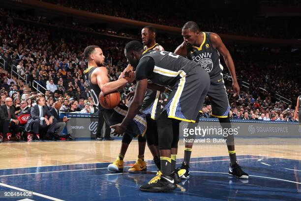 Kevin Durant assists Stephen Curry of the Golden State Warriors up during the game against the New York Knicks on February 26 2018 at Madison Square...