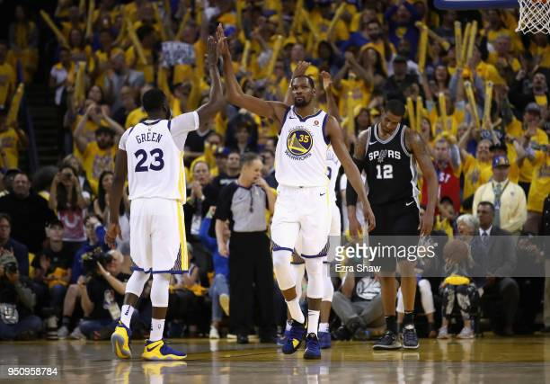 Kevin Durant high fives Draymond Green of the Golden State Warriors after LaMarcus Aldridge of the San Antonio Spurs turned the ball over in the...