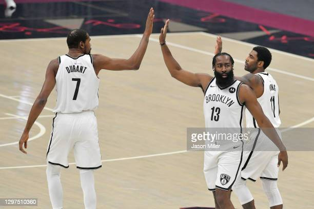 Kevin Durant James Harden and Kyrie Irving of the Brooklyn Nets celebrate during the first quarter against the Cleveland Cavaliers at Rocket Mortgage...