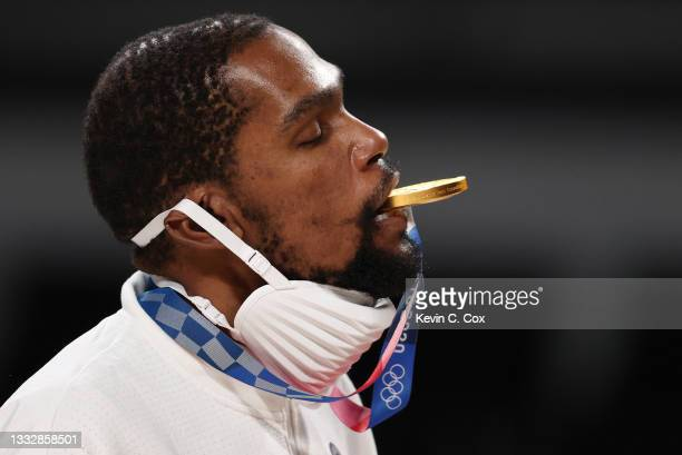 Kevin Durant of Team United States bites his gold medal during the medal ceremony for Men's Basketball at the Tokyo 2020 Olympic Games at Saitama...