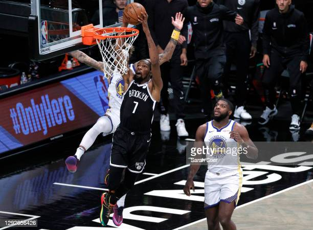Kevin Durant of the Brooklyn Nets dunks as Kelly Oubre Jr. #12 and Eric Paschall of the Golden State Warriors defend during the first half at...