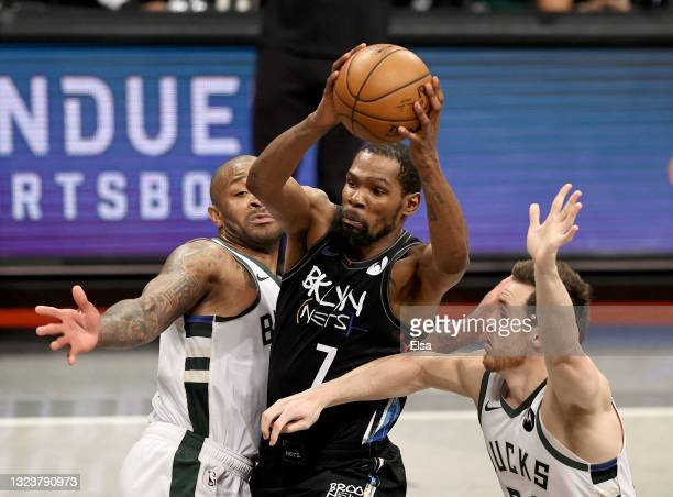 Kevin Durant of the Brooklyn Nets heads for the net as P.J. Tucker and Pat Connaughton of the Milwaukee Bucks defend during game 5 of the Eastern...