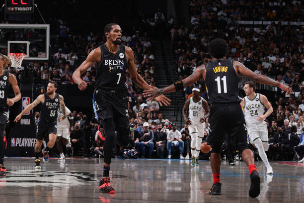 Kevin Durant of the Brooklyn Nets high fives Kyrie Irving of the Brooklyn Nets during Round 2, Game 2 of the 2021 NBA Playoffs on June 7, 2021 at...