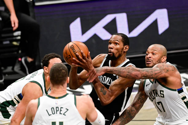 Kevin Durant of the Brooklyn Nets is defended by P.J. Tucker of the Milwaukee Bucks in Game One of the Second Round of the 2021 NBA Playoffs at...