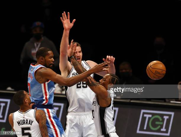 Kevin Durant of the Brooklyn Nets passes the ball as Jakob Poeltl and DeMar DeRozan of the San Antonio Spurs defend in the first quarter at Barclays...