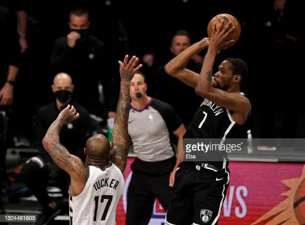 Kevin Durant of the Brooklyn Nets takes a shot to tie the game and force overtime as P.J. Tucker of the Milwaukee Bucks defends in the final seconds...