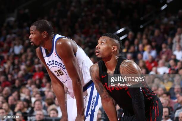 Kevin Durant of the Golden State Warriors and Damian Lillard of the Portland Trail Blazers look on during the game between the two teams on March 9...