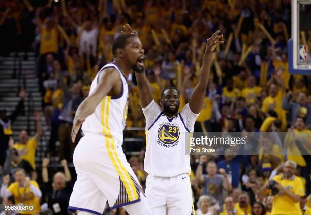 Kevin Durant of the Golden State Warriors and Draymond Green react after Stephen Curry made a shot against the New Orleans Pelicans during Game Five...