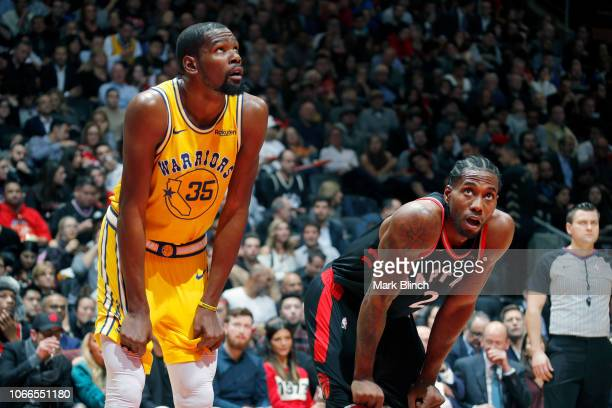 Kevin Durant of the Golden State Warriors and Kawhi Leonard of the Toronto Raptors look on during the game on November 29 2018 at Scotiabank Arena in...