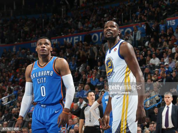 Kevin Durant of the Golden State Warriors and Russell Westbrook of the Oklahoma City Thunder looks on on November 22 2017 at Chesapeake Energy Arena...