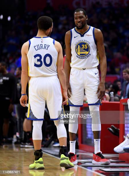 Kevin Durant of the Golden State Warriors and Stephen Curry laugh during a timeout during Game Two of Round One of the 2019 NBA Playoffs at Staples...