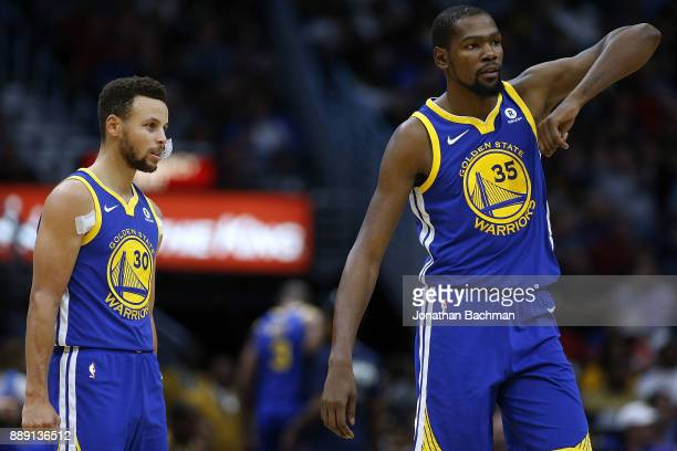 Kevin Durant of the Golden State Warriors and Stephen Curry react during the first half of a game against the New Orleans Pelicans at the Smoothie...