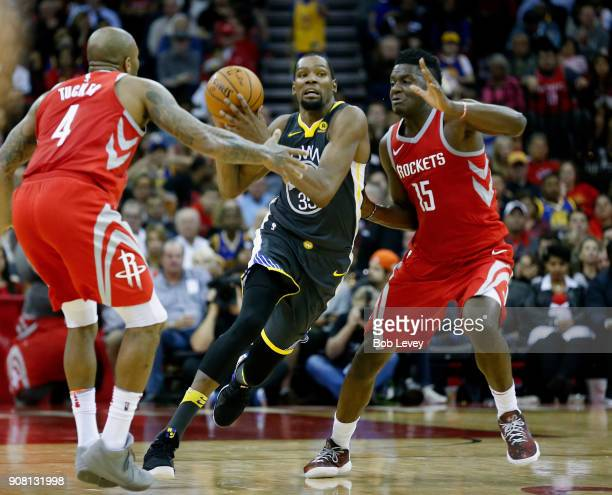 Kevin Durant of the Golden State Warriors attempts to get the shot off before the half as Clint Capela of the Houston Rockets and PJ Tucker defend at...