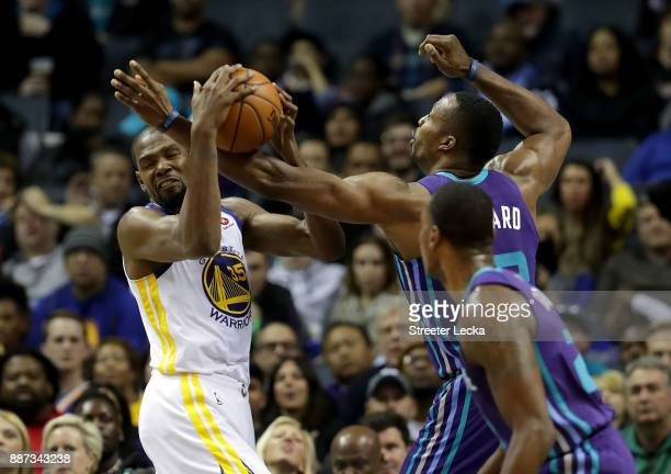 Kevin Durant of the Golden State Warriors battles for a loose ball against Dwight Howard of the Charlotte Hornets during their game at Spectrum...