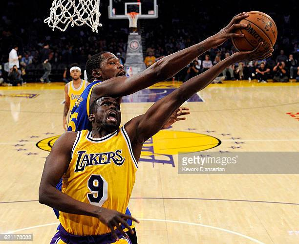Kevin Durant of the Golden State Warriors blocks a layup by Luol Deng of the Los Angeles Lakers during the first half of the basketball game at...