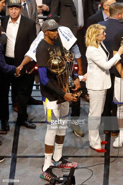 Kevin Durant of the Golden State Warriors celebrate on stage with the Bill Russell Finals MVP Trophy and the Larry O'Brien Championship Trophy after...