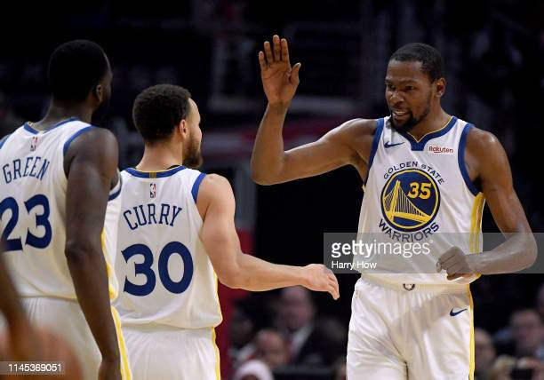 Kevin Durant of the Golden State Warriors celebrates a double digit lead lead over the LA Clippers with Stephen Curry and Draymond Green in the first...