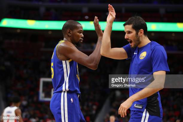 Kevin Durant of the Golden State Warriors celebrates a second half basket with Omri Casspi while playing the Detroit Pistons at Little Caesars Arena...