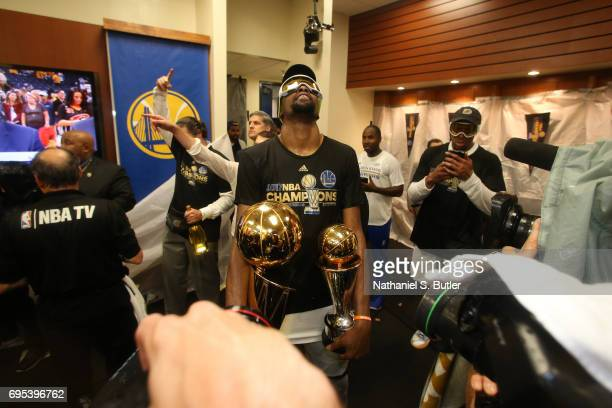 Kevin Durant of the Golden State Warriors celebrates and holds the Larry O'Brien Trophy and the Bill Russell Finals MVP Trophy in the locker room...
